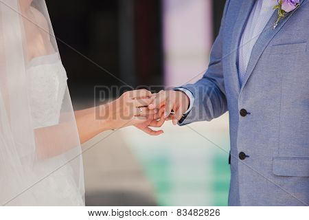 Groom wearing the Diamond ring to bride hand in wedding ceremony.