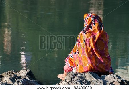Indian Woman In Sari Sits On A Rock At The River Ganga