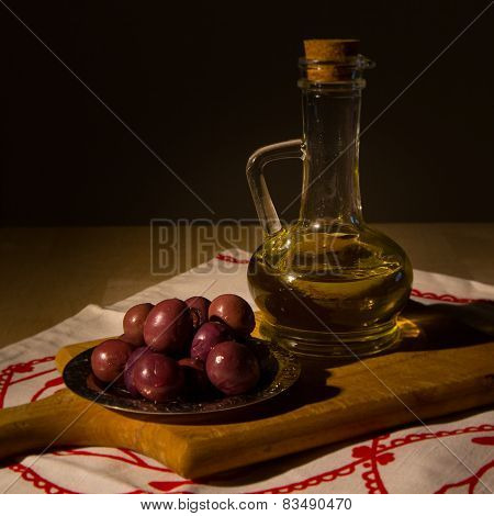 jar with olive oil and some olives