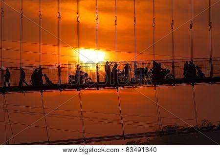 People On Ram Jhula Bridge At Sunset
