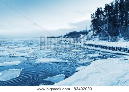 Winter Coastal Landscape With Floating Ice And Frozen Pier