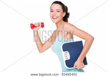 Fit woman holding dumbbell and weighs