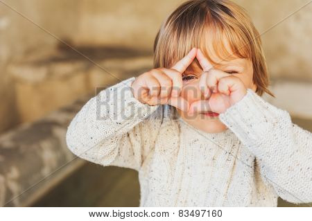 Outdoor portrait of a cute toddler boy pretending to take a picture with his hands