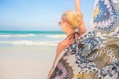pic of flutter  - Happy woman enjoying, relaxing joyfully in summer by tropical blue water. Her colorful kerchief fluttering in wind on picture perfect Paje beach, Zanzibar, Tanzania. ** Note: Soft Focus at 100%, best at smaller sizes - JPG
