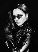 image of gun shot  - Black and white image of secret agent woman with gun in hand on black background - JPG