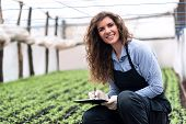 image of genetic engineering  - Beautiful young biotechnology woman engineer with clipboard and pen - JPG