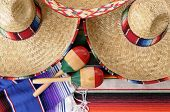 foto of mexican fiesta  - Mexican scene with sombrero straw hat maracas and traditional serape blanket or rug - JPG