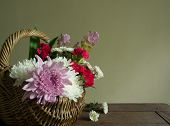 foto of gift basket  - Basket of flowers as a gift placed on a wooden table - JPG