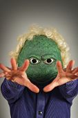 stock photo of unnatural  - Creepy bald lizard man wearing a blue sweater - JPG