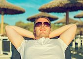 picture of sunbather  - Man sunbathing lying on the beach - JPG