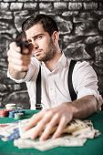 picture of gangster  - View of a gangster man is playing poker and holding a gun - JPG