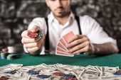 foto of gangster  - Close-up hand of young gangster man while playing poker game with money chips and cards. ** Note: Shallow depth of field - JPG
