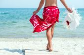 image of ankle shoes  - Beautiful woman with white hat walks at the sea side in red dress - JPG