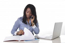 image of secretary  - black African American ethnicity woman working hard as secretary in stress talking on mobile phone multitasking sitting at work office desk with computer laptop in women business concept - JPG
