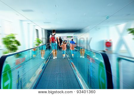 Father And Son Moving On Escalator After Arrival In International Airport