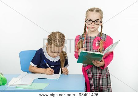 The Student Writes In A Notebook Under Supervision Of Teacher