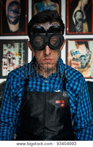 Tattooist In Welder Glasses And Leather Apron