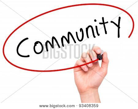 Man Hand writing Community with marker on transparent wipe board.