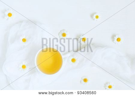Teacup of natural chamomile herbal tea on white kitchen table background