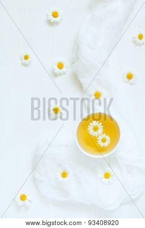 White cup of natural dried chamomile tea with blooming camomile flowers on white kitchen table backg