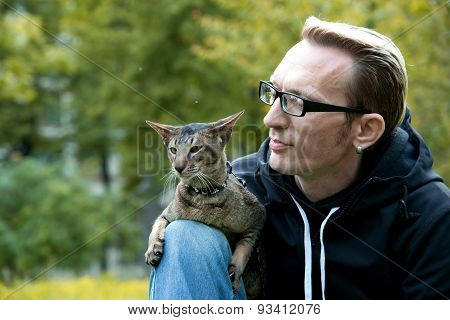 cat sits on the man's lap