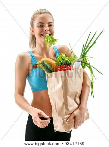 Happy Cutie Athletic Woman With Lettuce In Her Mouth And Grocery Bag Full Of Healthy Fruits