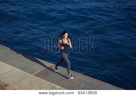 Cute young energetic woman jogging outdoors along the coastline at sunny day