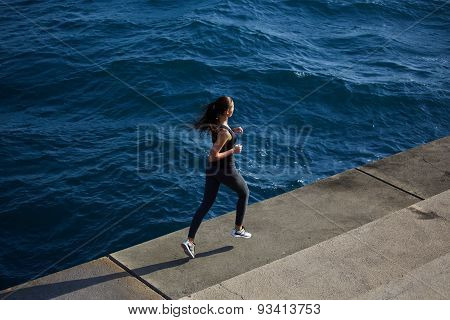Young sporty woman dynamic running outdoors along the seashore at sunny summer day