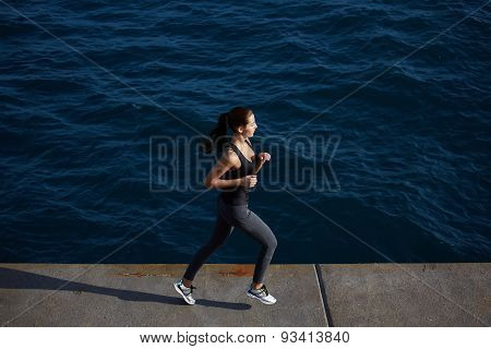 Young sporty girl in action running along the beach with amazing big ocean waves on background