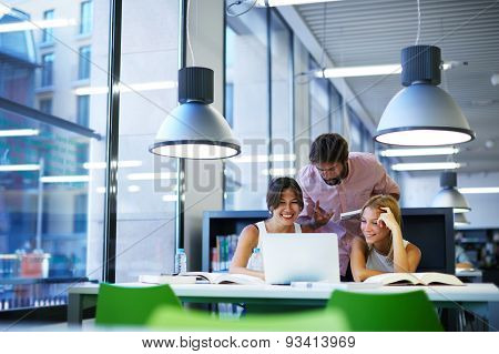 International university students having fun studying in library while sitting at the desk table