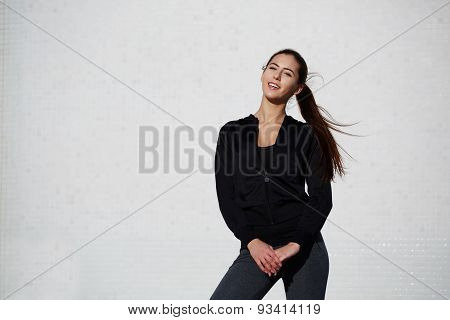 Athletic healthy girl dressed in sportswear posing outdoors at beautiful sunny day