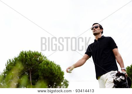 Low angle portrait of professional golf player walking to the next hole holding bag for clubs