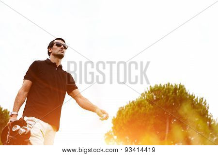 Portrait of professional golf player walking to the next hole holding bag for clubs good golf game