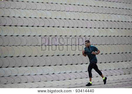 Portrait of athletic dark-skinned man running along beautiful grey wall outdoors in the park