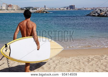 Rear view attractive man with sexy body going to the sea holding big copy space surfing board