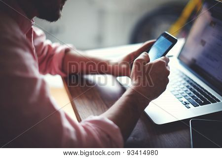 Rear view of business man hands busy using cell phone at office desk