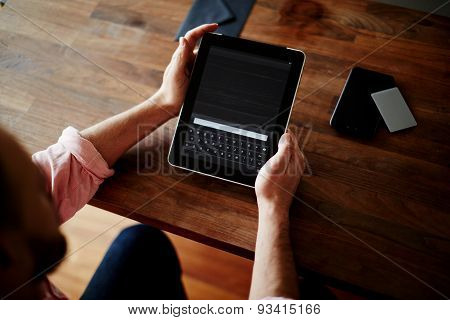 Cropped shot of a man's hands using a digital tablet at cowering office online shopping at home