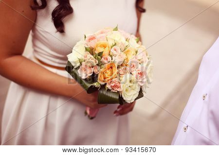 Bride Holding Bouquet Of Roses