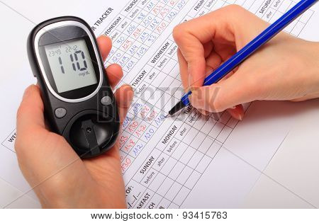 Hand Of Woman Writing Data From Glucometer To Medical Form