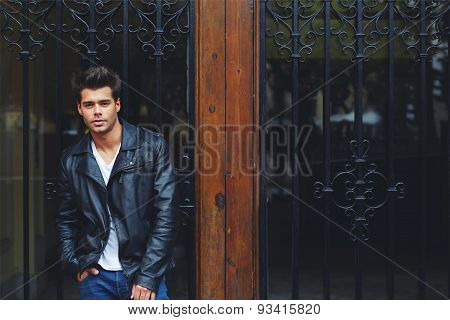 Portrait of a handsome fashionable male in trendily clothing posing outdoors in the city