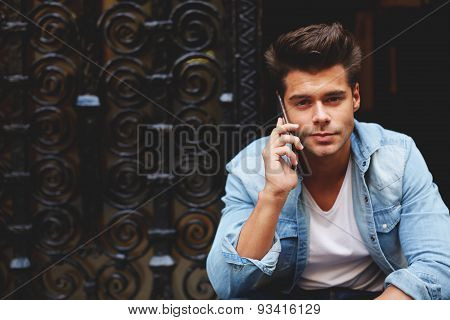 Portrait of an attractive man talking on his smart phone looking to the camera and enjoy the spring