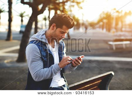 Stylish brunette hipster using cell phone reading text messages at sunny evening