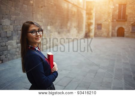 Portrait of beautiful young student standing outside holding her book smiling