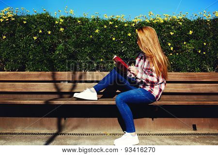 Attractive blonde hair young woman enjoying the sun at beautiful day outdoors while read book