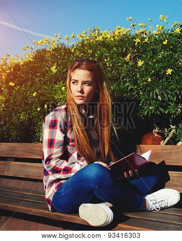 Charming girl relaxing in the spring park while sitting on wooden bench at campus reading a book