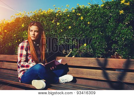 Young woman reading book while enjoying the sun at beautiful day outdoors filter sun
