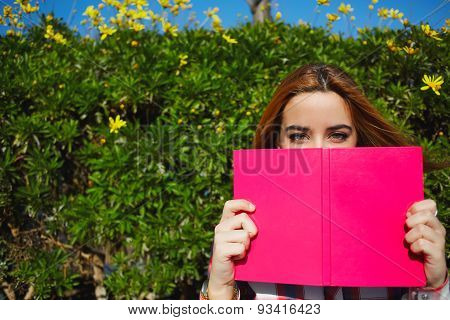 Beautiful young student covering half face with a pink book while looking to you