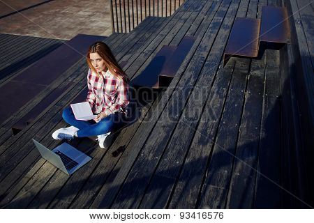 Attractive young woman using laptop sitting on wooden staircase enjoying sunny day outdoors