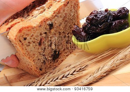 Slicing Fresh Bread, Dried Plums And Ears Of Wheat