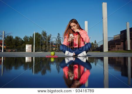Young girl sitting near the fountain which reflects her image and prints a message on mobile phone